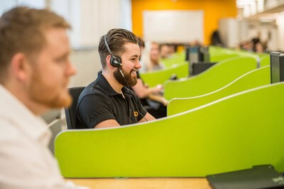 Employees wearing headsets working in a call centre