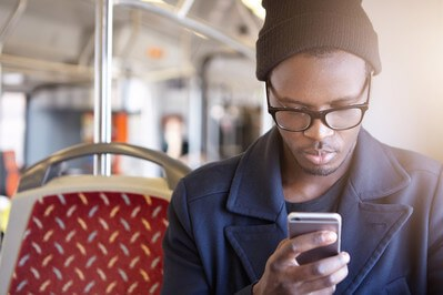 Man looks at mobile phone whilst on the bus